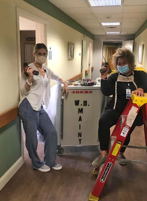 Two female staff with protective masks posing with electric drills