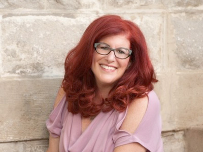 Lady with red hair, glasses and pink shirt smiling